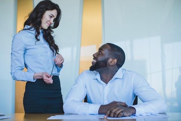 Compañeros de trabajo sonriendo uno al otro Foto gratis