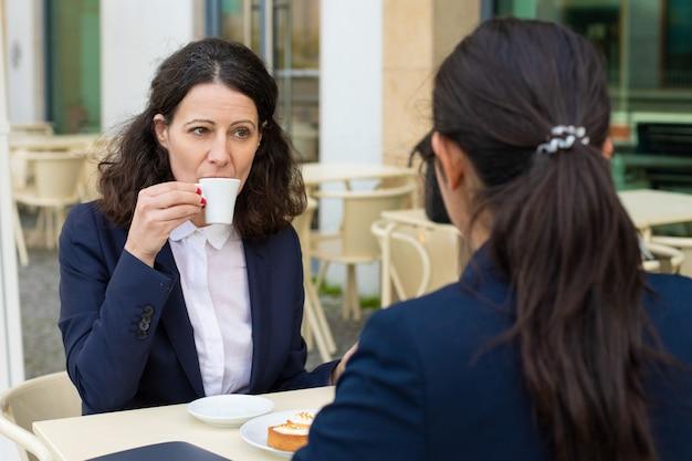 Compañeros de trabajo tomando café en la cafetería al aire libre Foto gratis