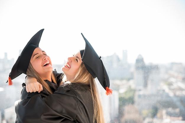 Compañeros de la vista frontal abrazando en la ceremonia Foto gratis