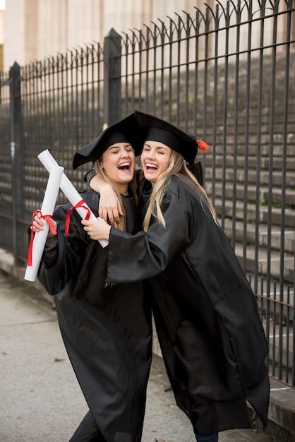 Compañeros de la vista frontal abrazando en la graduación Foto gratis