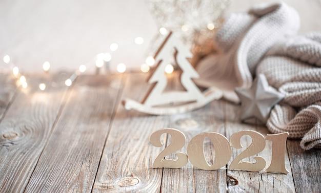 Composición de año nuevo festivo con número de año nuevo de madera sobre un fondo borroso claro con decoración navideña. Foto gratis
