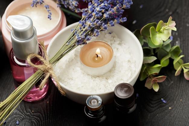 Composición aromática de lavanda, hierbas, cosméticos y sal sobre una mesa oscura Foto Premium
