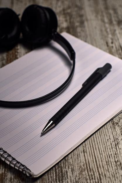 Composición de los auriculares negros al lado de un cuaderno de pentagrama vacío en una mesa de madera Foto Premium