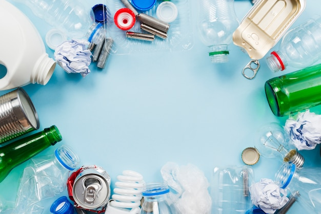 Composición de la basura para el reciclaje sobre fondo azul Foto gratis