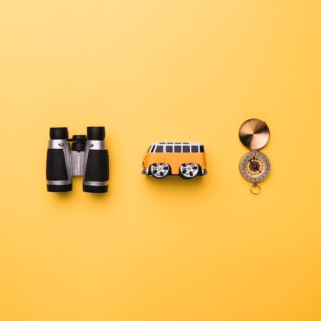 Composición de binoculares bus pequeño juguete y brújula Foto gratis