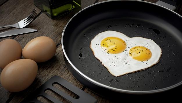 Composición de cocción, huevo en forma de corazón con dos yemas en una sartén. Foto Premium