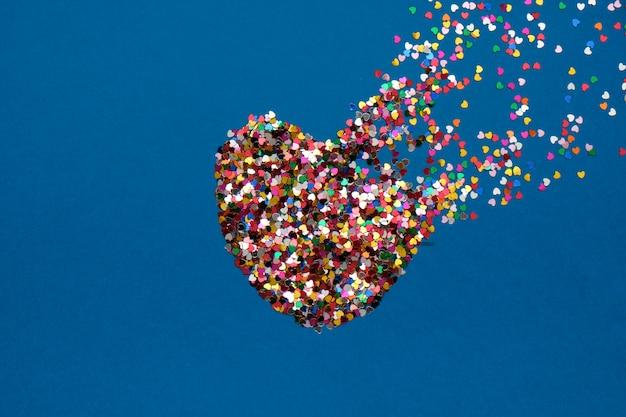 Composición del día de san valentín con corazón roto hecho de confeti sobre fondo azul clásico Foto Premium
