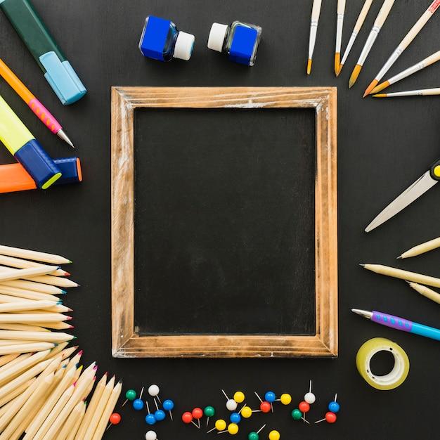 Composición divertida con material escolar y marco de madera ...