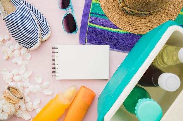 Composición fantástica con cuaderno en blanco y elementos veraniegos Foto gratis