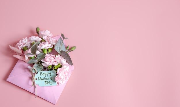 Composición festiva con un sobre con flores frescas y la inscripción feliz día de la madre. Foto gratis