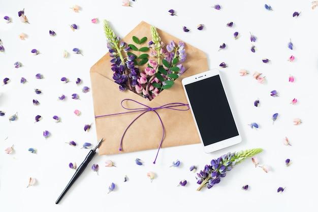 Composición festiva: sobre una mesa blanca se encuentra un sobre, cuaderno, bolígrafo y flores. Foto Premium