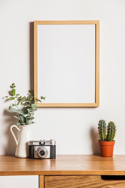 Composición floral con marco y cámara Foto Gratis