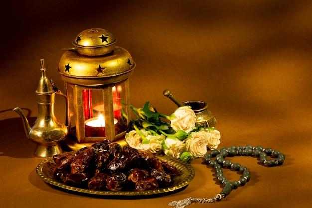 Composición islámica con dátiles secos y linterna. Foto gratis