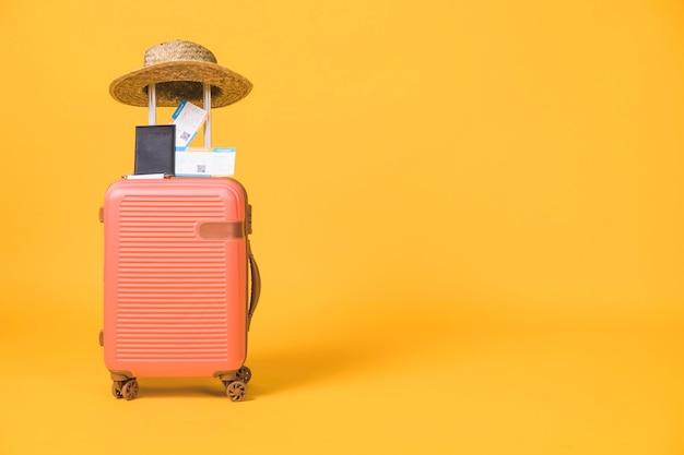 Composición de maleta y tickets de pasaporte y sombrero sobre la misma. Foto gratis