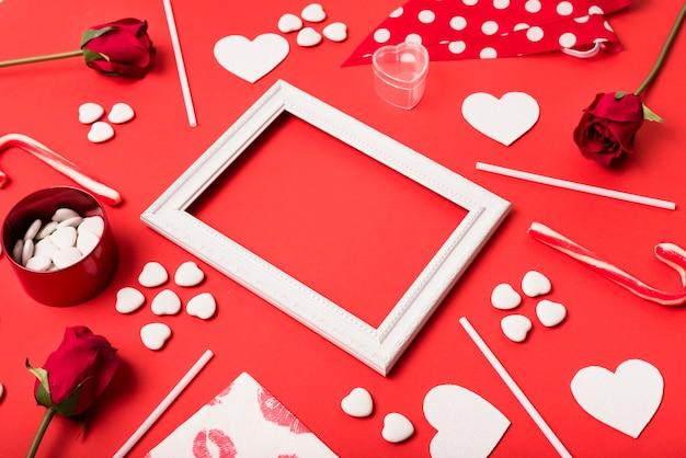 Composición del marco de fotos entre corazones de papel, flores y varitas. Foto gratis