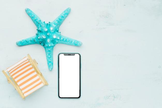 Composición marina con teléfono móvil sobre fondo claro. Foto gratis