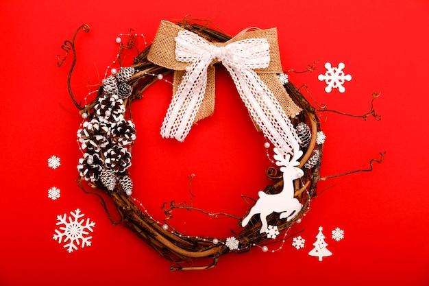 Composición navideña. corona hecha a mano sobre fondo rojo. lay flat, vista superior, espacio de copia, cuadrado. corona de adviento o navidad Foto Premium