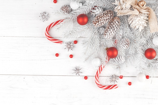 Composición navideña. marco hecho de ramas de abeto sobre fondo blanco de madera Foto Premium