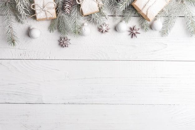 Composición navideña con marco de ramas de abeto, adornos navideños y piñas. vista plana, vista superior Foto Premium