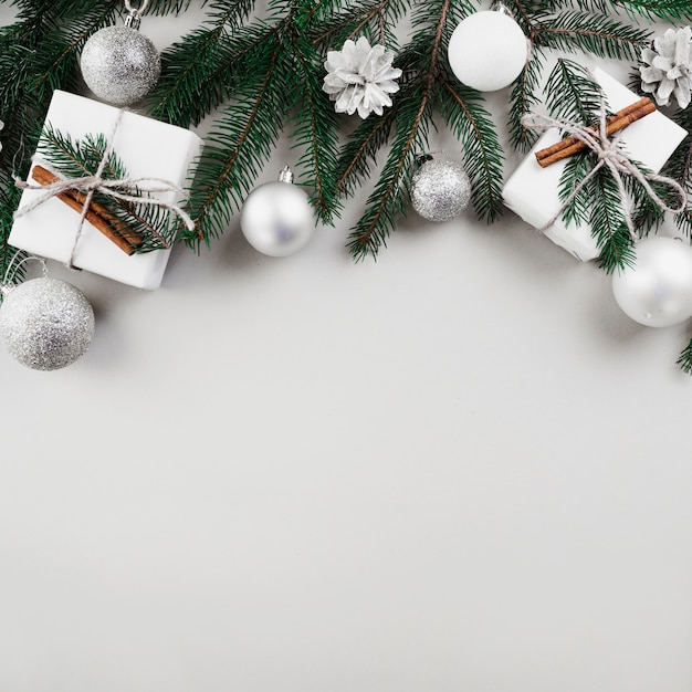 Composición navideña de ramas de abeto con adornos de plata. Foto gratis