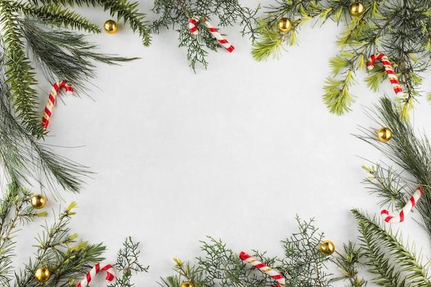 Composición navideña de ramas con bastones de caramelo. Foto gratis