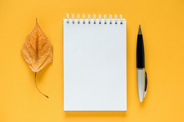 Composición de otoño. bloc de notas en blanco blanco, hoja de naranja seca y pluma en amarillo. Foto Premium