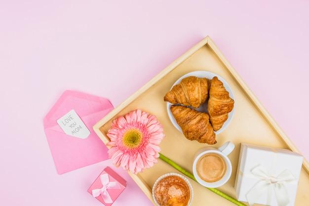 Composición de panadería, flor y presente en bandeja cerca de sobre con etiqueta Foto gratis