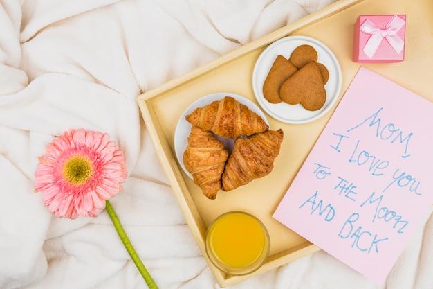 Composición de panadería, vidrio y papel con palabras en la bandeja cerca de la flor Foto gratis