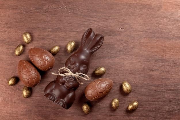 Composición de pascua con huevos de chocolate y conejito sobre fondo de madera Foto Premium