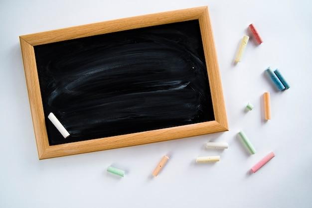 Composición de pizarra vacía y coloridas tizas. Foto gratis