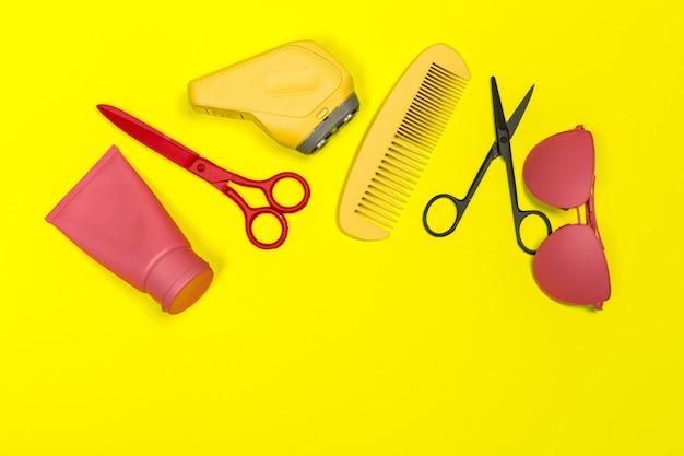 Composición plana laico con herramientas de peluquero profesional sobre fondo amarillo Foto Premium