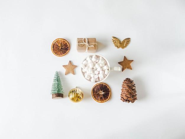 Composición plana de navidad: galleta de estrella, regalo, rodajas de naranja seca, taza con bebida caliente y malvaviscos, piña y abeto de navidad Foto Premium