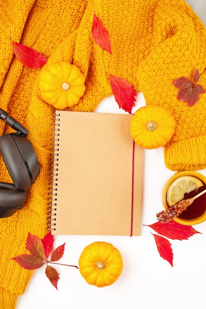 Composición plana de otoño con hojas de otoño, una taza de té caliente y un cálido suéter naranja de lana Foto Premium
