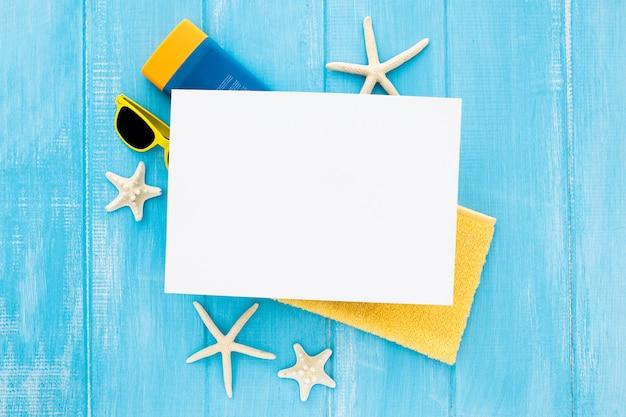 Composición plana para verano con botella de crema de estrellas de mar, gafas, toalla y cartón en blanco Foto gratis