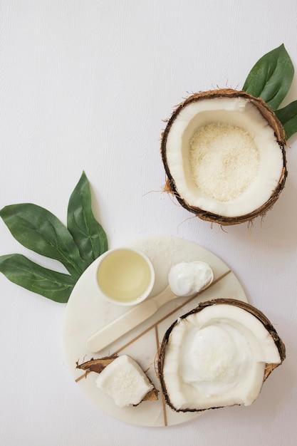Composición de productos cosméticos a base de hierbas de coco con tarjeta en blanco y hojas verdes sobre superficie blanca Foto gratis