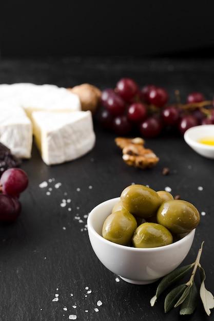Composición de queso y aceitunas de alto ángulo sobre fondo negro Foto gratis
