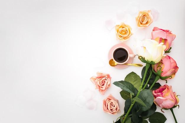 Composición romántica con rosas, pétalos y una taza de café rosa con espacio de copia Foto gratis
