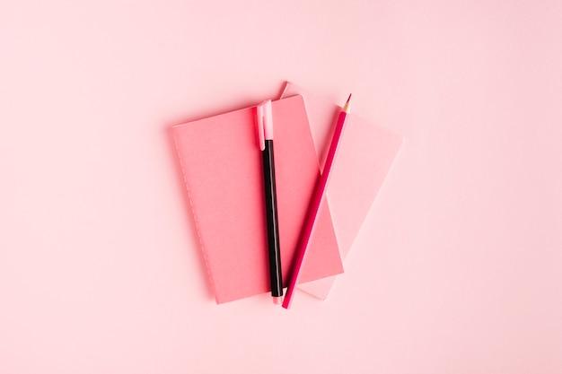 Composición rosa con cuaderno y papelería en escritorio Foto gratis