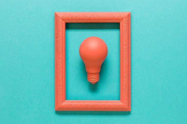 Composición rosa con lámpara en marco sobre superficie azul. Foto gratis