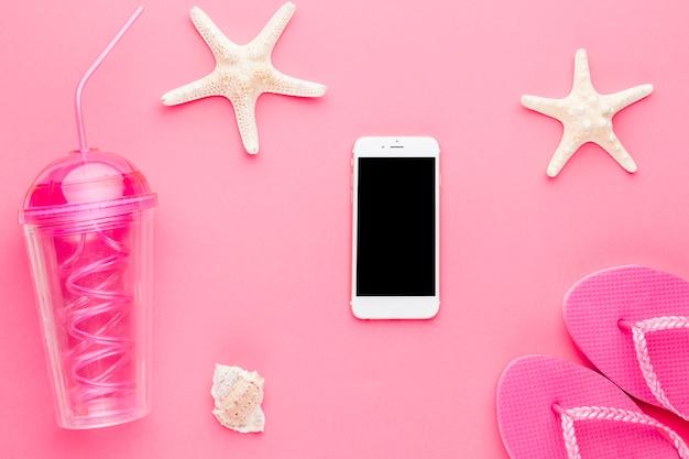 Composición de smartphone coctel estrella de mar y chanclas Foto gratis