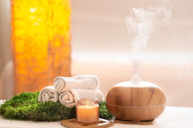 Composición de spa con aroma de moderno difusor de aceite con productos para el cuidado corporal. toallas blancas retorcidas, verdes primaverales y flores. concepto de spa para el cuerpo y la salud. Foto gratis