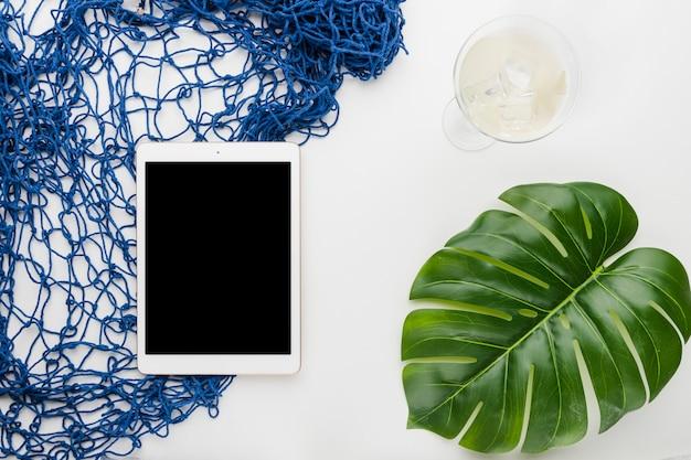 Composición de tableta bebida monstera hoja y mallas. Foto gratis