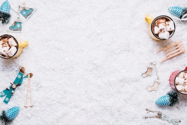 Composición de tazas cerca de juguetes navideños entre nieve Foto gratis