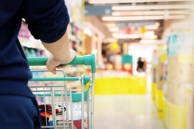 Comprador femenino con carro con movimiento borroso de grandes almacenes de supermercado Foto Premium