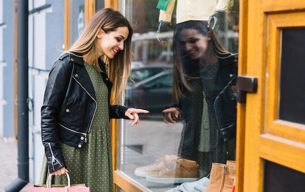 Compras femeninas jovenes sonrientes de la ventana Foto gratis