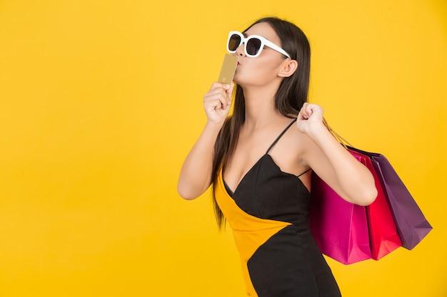 Compras hermosa mujer con gafas con una tarjeta de crédito de oro con una bolsa de papel de colores en un amarillo. Foto gratis