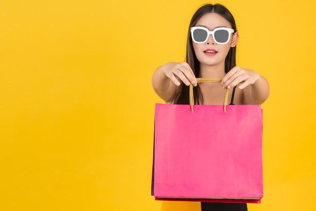 Compras de hermosas mujeres con gafas con bolsas de papel de colores sobre un fondo amarillo. Foto gratis