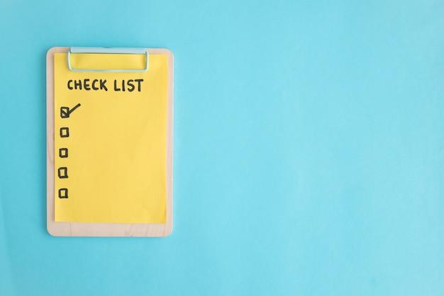 Compruebe el papel de la lista en el sujetapapeles de madera sobre el fondo azul Foto gratis