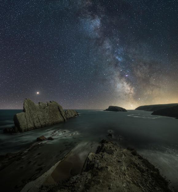 Compuesto de paisaje nocturno en la playa de la costa norte de españa. Foto Premium