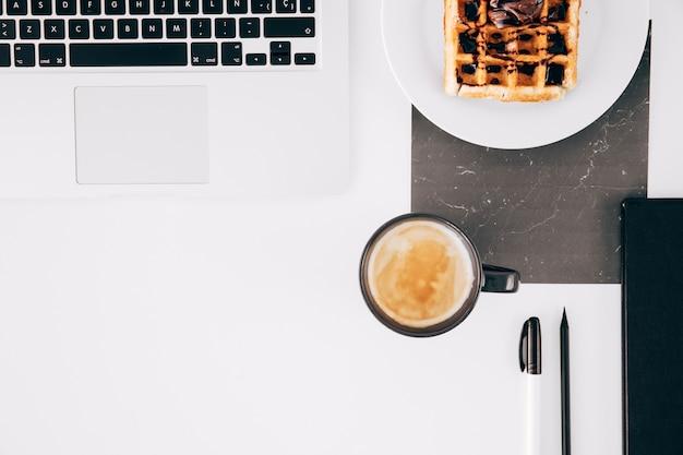 Una computadora portátil abierta; gofre; taza de café; lápiz; pluma y portátil abierto en escritorio blanco Foto gratis